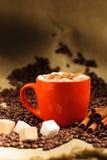 Taza anaranjada con cuppuccino caliente Imagenes de archivo
