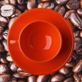 Taza anaranjada en los granos de café. Fotos de archivo libres de regalías