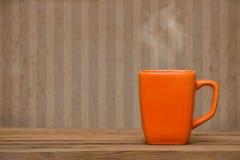 Taza anaranjada en una tabla de madera sobre el papel pintado del grunge Fotos de archivo libres de regalías