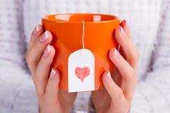 Taza anaranjada hermosa con la bolsita de té del amor Imagen de archivo libre de regalías