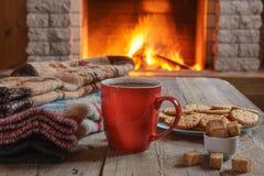 Taza anaranjada para el té o el café; las cosas de las lanas acercan a la chimenea acogedora imagen de archivo