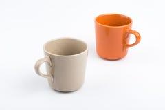 Taza anaranjada y taza marrón Imagen de archivo