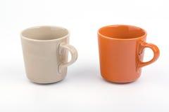 Taza anaranjada y taza marrón Fotos de archivo libres de regalías