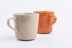 Taza anaranjada y taza marrón Imágenes de archivo libres de regalías