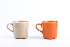Taza anaranjada y taza marrón Fotos de archivo