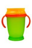 Taza anaranjada y verde del plástico del bebé. Fotografía de archivo