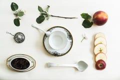 Taza, atasco, manzana y rama con las flores en una tabla blanca Fotografía de archivo libre de regalías