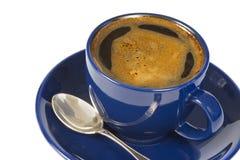 Taza azul con café en el fondo blanco. Fotos de archivo