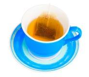 Taza azul con un bolso de té aislado en blanco Imagenes de archivo