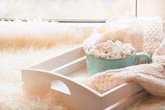 Taza azul de chocolate caliente con la melcocha en el alféizar blanco con la peletería para el día de fiesta del resto Fotografía de archivo libre de regalías