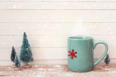 Taza azul del té de la Navidad con el copo de nieve rojo y los abetos miniatura encendido Fotografía de archivo libre de regalías