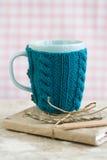 Taza azul en un suéter azul que se coloca en un cuaderno viejo Imágenes de archivo libres de regalías