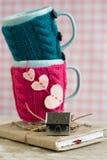 Taza azul en un suéter rosado que se coloca en un cuaderno viejo Imagen de archivo libre de regalías