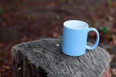 Taza azul para el caf?, colocada en un registro imagen de archivo libre de regalías
