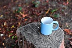 Taza azul para el caf?, colocada en un registro fotografía de archivo libre de regalías