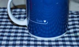 Taza azul y blanca con adorno del amor aislada imagen de archivo