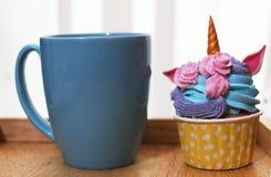 Taza azul y magdalena del color en colores pastel del unicornio en la bandeja de madera imagen de archivo libre de regalías
