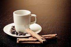 Taza blanca con café cerca de los granos de café sobre la tabla de madera Imagen de archivo
