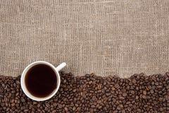 Taza blanca con café en la arpillera fotografía de archivo