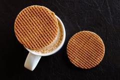Taza blanca con café espumoso lechoso y una galleta redonda de la galleta encendido Fotografía de archivo