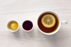 Taza blanca con el té y el limón, miel del atasco Fotografía de archivo