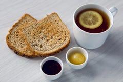 Taza blanca con el té y el limón, miel del atasco Imagen de archivo