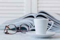 Taza blanca con la bebida y la revista de la mañana en la tabla de madera Imagenes de archivo