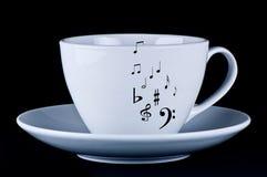 Taza blanca con las notas musicales negras Foto de archivo