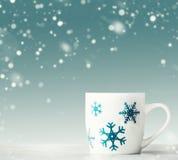 Taza blanca con los copos de nieve azules en la tabla blanca en el fondo azul con las nevadas, vista delantera Invierno feliz fotos de archivo libres de regalías