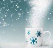 Taza blanca con los copos de nieve azules en la tabla blanca en el fondo azul con la nieve y el bokeh, vista delantera imágenes de archivo libres de regalías