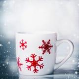 Taza blanca con los copos de nieve rojos en las nevadas azules fondo, vista delantera Tarjeta feliz de las vacaciones de invierno Fotografía de archivo libre de regalías