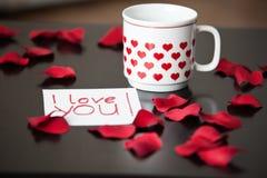Taza blanca con los corazones rojos y una Yo-amor-usted-nota sobre una tabla negra, rodeada por los pétalos color de rosa rojos Imagen de archivo libre de regalías