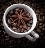 Taza blanca con los granos de café y el anís de estrella fotos de archivo