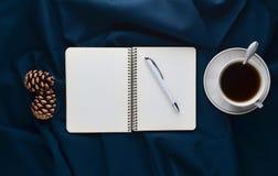 Taza blanca con té, cuaderno y pluma, conos del pino en una hoja oscura Consumición del té de la mañana del invierno Visión super Fotografía de archivo