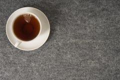 Taza blanca con té en un fondo negro Visión superior fotos de archivo