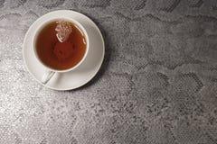 Taza blanca con té en un fondo negro Visión superior imagen de archivo