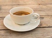 Taza blanca con un café express doble en una tabla de madera Foto de archivo