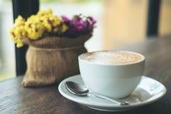 Taza blanca de café caliente del latte con las flores en un florero en la tabla de madera del vintage Imagenes de archivo
