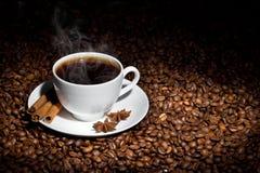 Taza blanca de café caliente en los granos de café Fotos de archivo libres de regalías