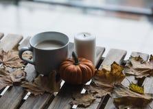 Taza blanca de café o de té cerca de una calabaza y de una vela Imagenes de archivo