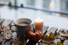 Taza blanca de café o de té cerca de una calabaza y de una vela Fotos de archivo libres de regalías