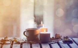 Taza blanca de café o de té cerca de velas con las hojas de arce Fotografía de archivo