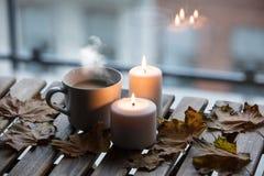 Taza blanca de café o de té cerca de velas con las hojas de arce Fotos de archivo