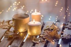 Taza blanca de café o de té cerca de velas con las hojas de arce Foto de archivo