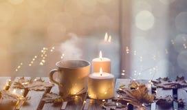 Taza blanca de café o de té cerca de velas con las hojas de arce Fotos de archivo libres de regalías