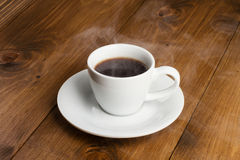 Taza blanca de café tórrido en la tabla de madera Imagen de archivo