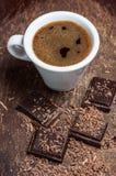 Taza blanca de café y de chocolate oscuro Foto de archivo