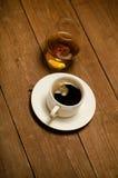 Taza blanca de café y de coñac en un vidrio en la tabla de madera vieja T Foto de archivo libre de regalías