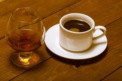 Taza blanca de café y de coñac en un vidrio en la tabla de madera vieja T foto de archivo