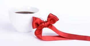 Taza blanca de coffe con el arqueamiento rojo Fotos de archivo libres de regalías